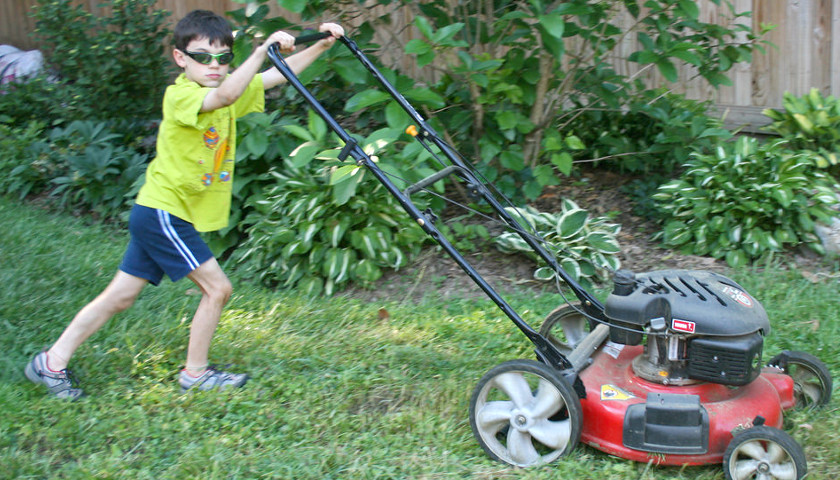 Kid mows the lawn