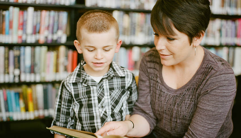 Teacher reading to student.