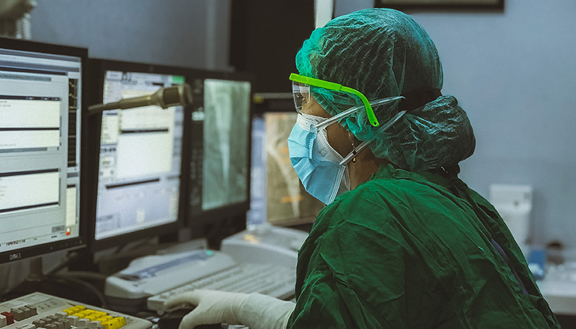 Person in green protective gear in lab with safety glasses and mask on