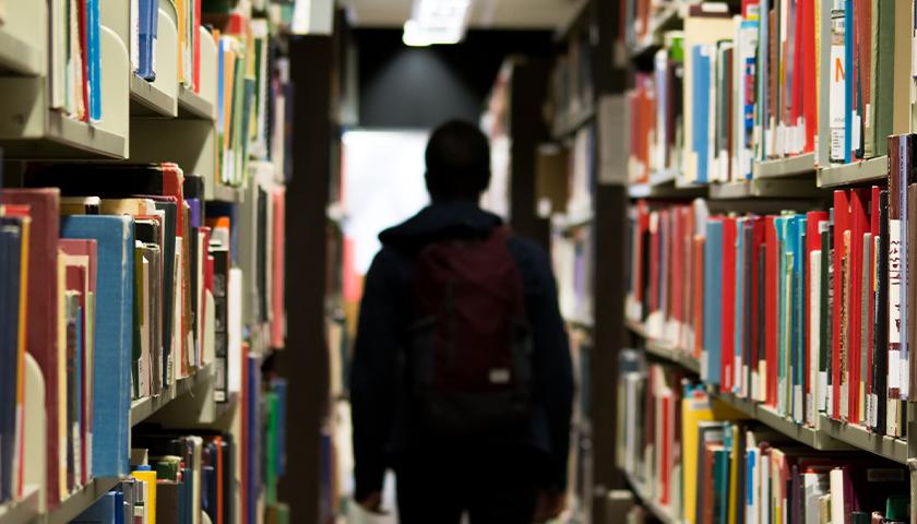 Person walking through library aisle