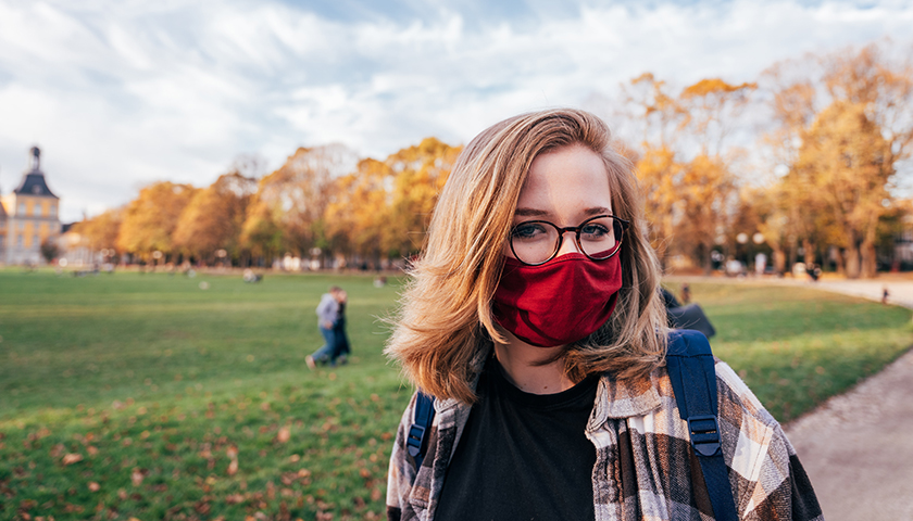 Student on campus wearing a mask outside.