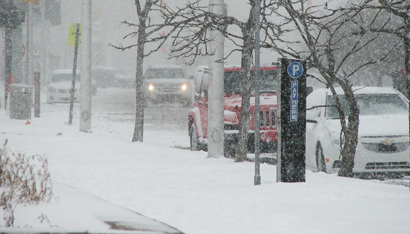 Sidewalk covered in snow and parked vehicles