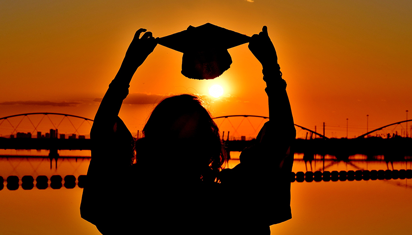 Silhouette of graduate holding up graduation cap