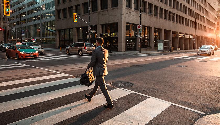 Man in business suit walking on crosswalk in city