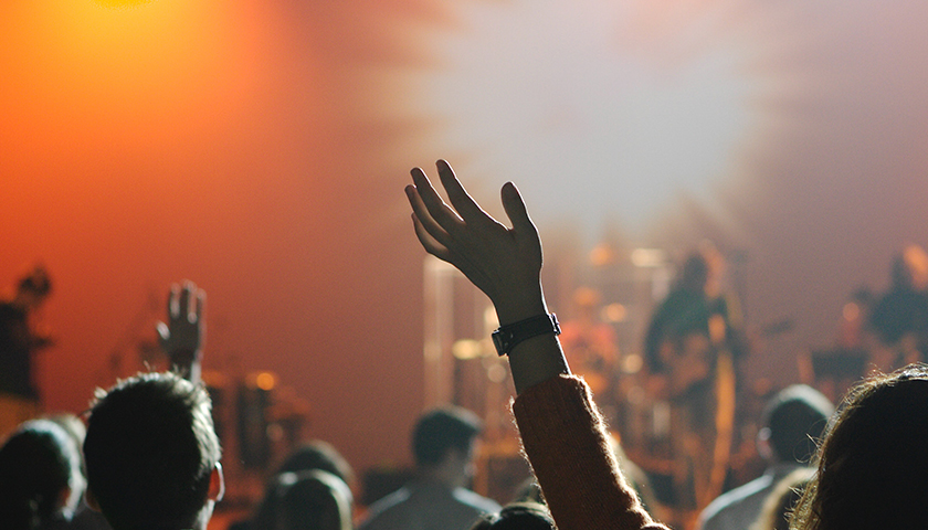 People holding hands in air at church worship service