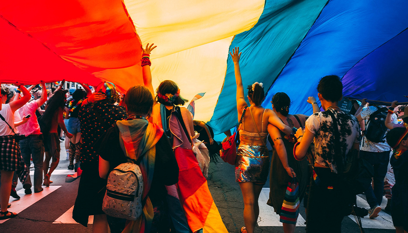 Pride Parade with group of people under large rainbow flag