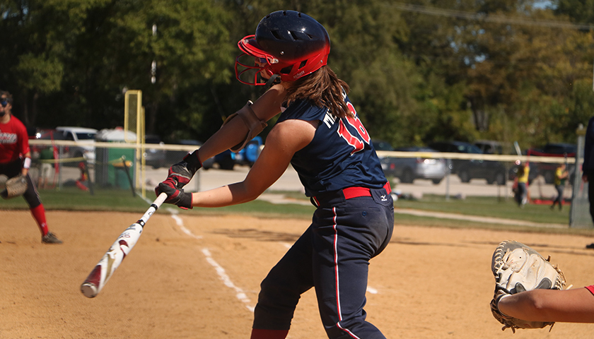 Girl up to bat, swinging her bat at a softball game.