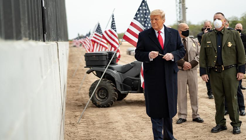 President Donald J. Trump prepares to sign a plaque placed along the border wall Tuesday, Jan. 12, 2021, at the Texas-Mexico border near Alamo, Texas.