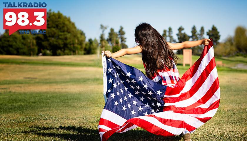 Girl holding U.S. flag, running in field