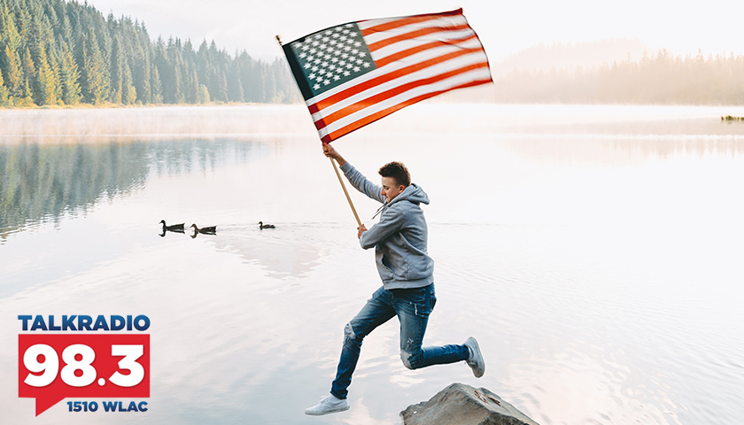 Man leaping onto rocks in lack, holding American flag
