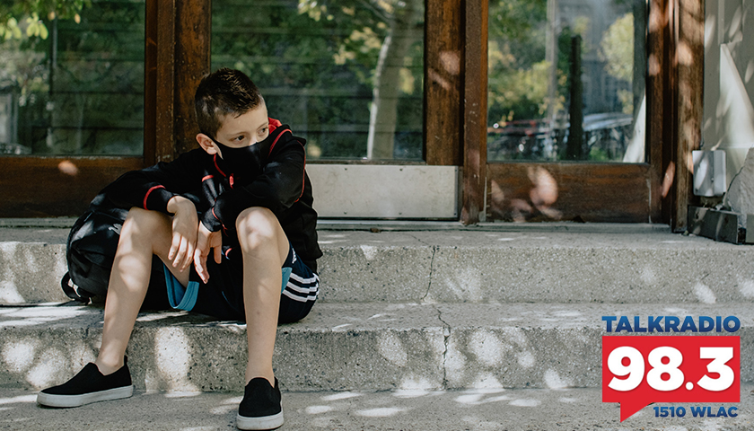 Young boy, sitting on steps with mask on