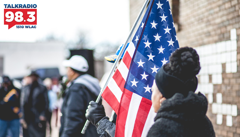 Person in a crowd, holding the American flag