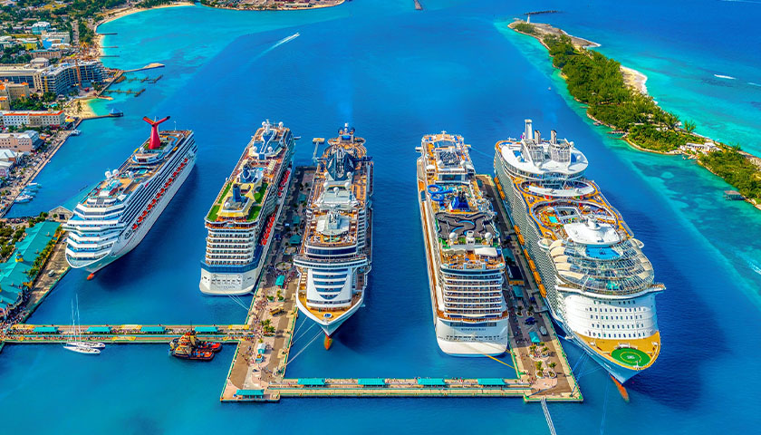 Aerial shot of several cruise ships in the ocean, clear water.