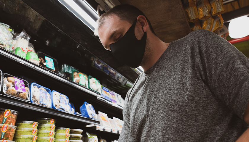Man at grocery store wearing a black mask