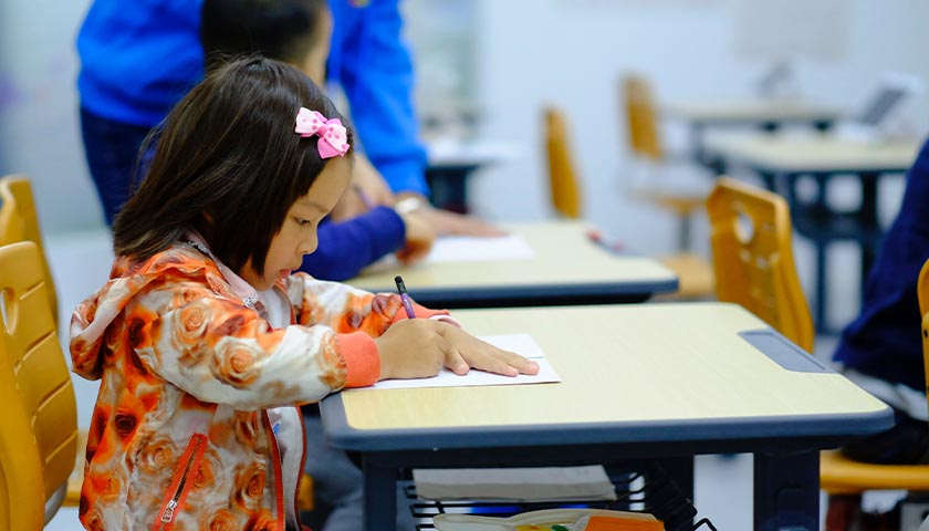 Young girl sitting at a desk, writing