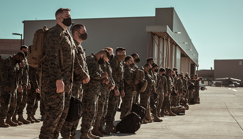 Large group of United States Military soldiers standing in straight line at a base