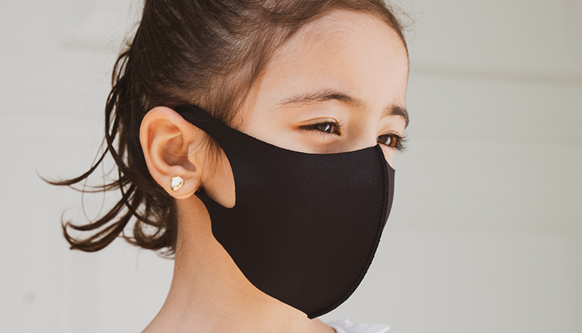 Young girl with brown hair wearing black mask