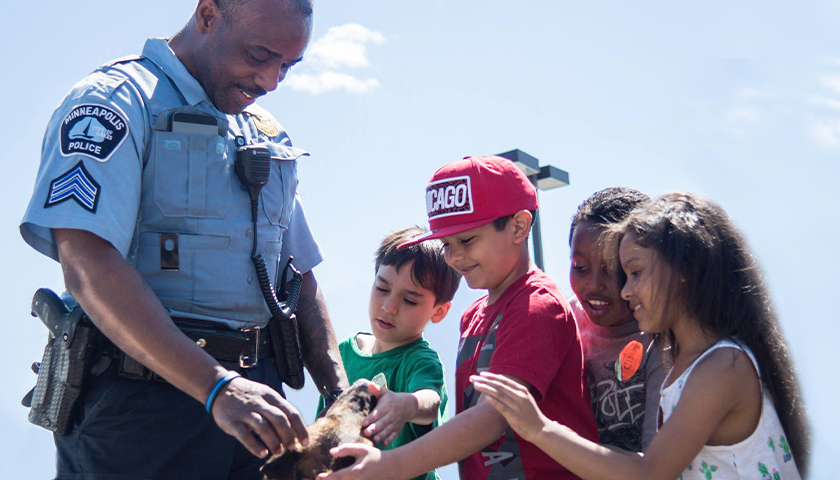 Minneapolis Police officer with dog and children