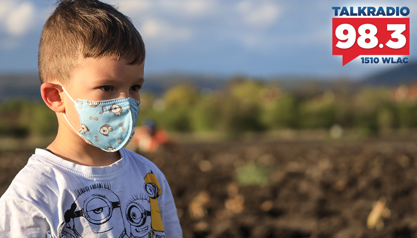 Young boy in white shirt with a mask on
