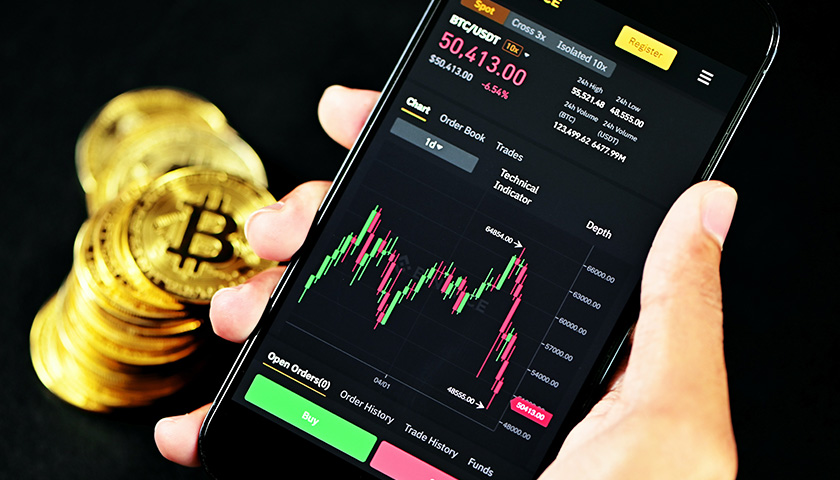 Person holding phone with cryptocurrency info on screen