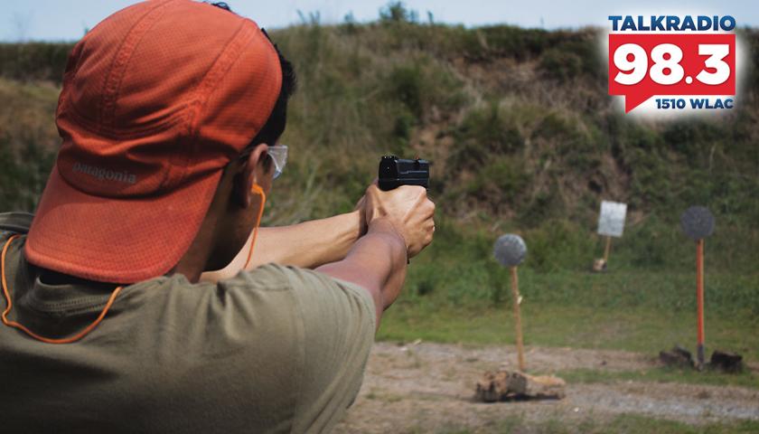 man shooting handgun at a gun range