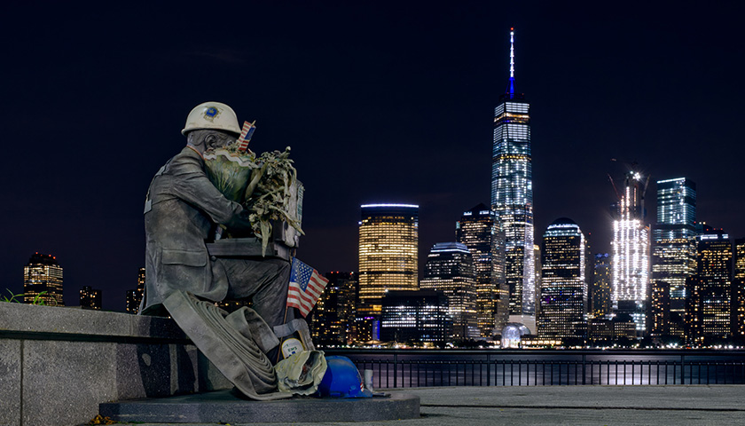 Across the water from NYC, with a first responder statue