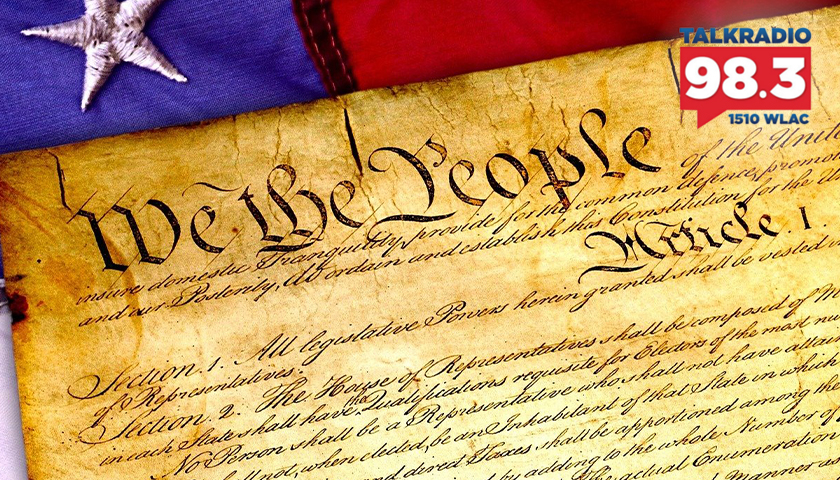 The U.S. Constitution with an American Flag behind it