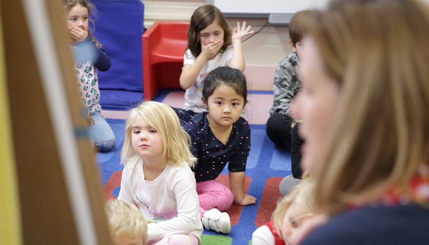 Students on the floor in the classroom, listening to the teacher read