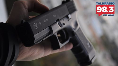 Person holding a Glock handgun in palm of hand