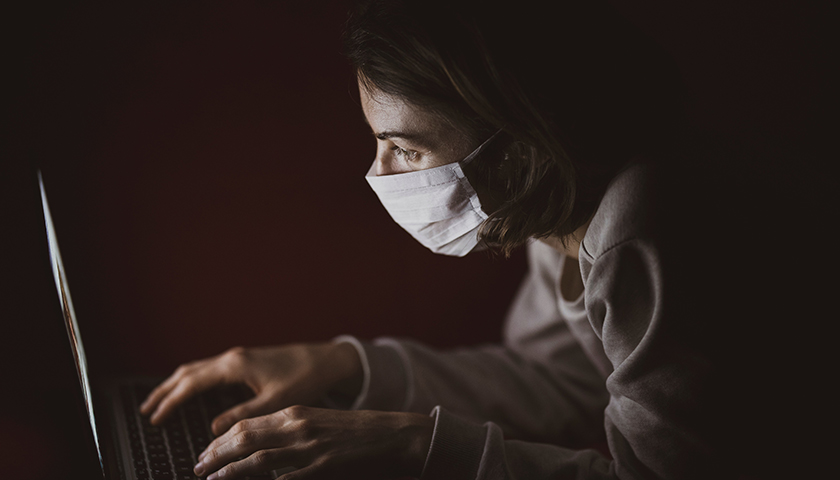 Woman in mask in the dark looking at computer screen