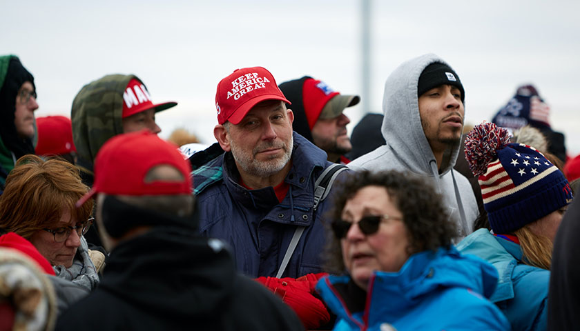 """Group of people at a Trump rally, man in a """"Keep America Great"""" hat"""