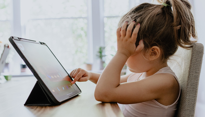 Young girl using an iPad to work on school assignments at kitchen table